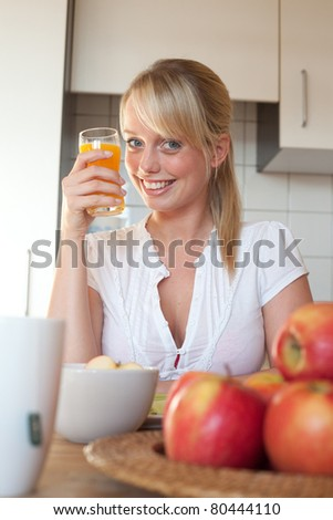 young blond woman with a glass of juice/young blond woman with a glass of juice in a kitchen