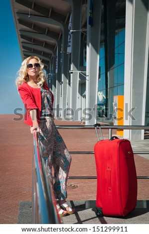 young blond woman with a red suitcase near airport - stock photo