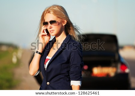 Young blond woman with broken car calling for help - stock photo