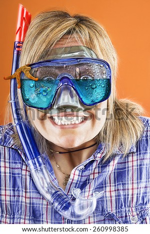 young blond woman with flooded scuba mask and snorkel making a funny face,open mouth and teeth bared, isolated on orange background