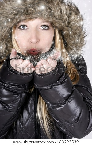 Young blond woman with furry hood and stardust - stock photo