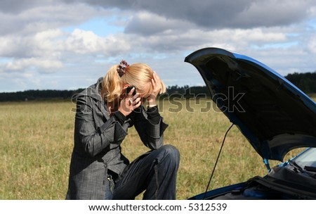 young blond woman with her broken car. The girl is crying - stock photo