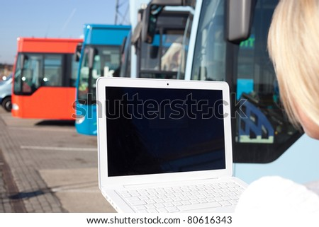 young blond woman with laptop in front of some busses/young blond woman stands with her laptop in front of a few busses
