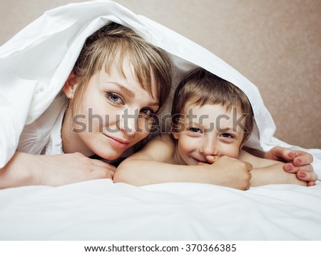 young blond woman with little boy in bed, mother and son, happy family