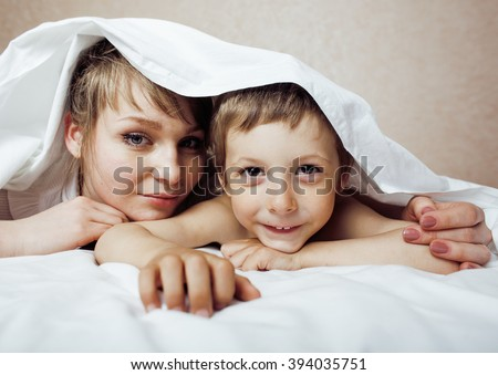 young blond woman with little boy in bed, mother and son, happy familyyoung blond woman with little boy in bed, mother and son, happy family