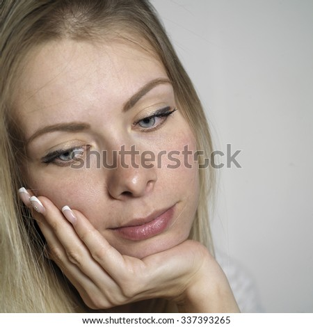 Young blond woman with long hair dreamily looking down, square studio shot