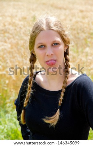 Young, blond woman with pigtails sticking out her tongue