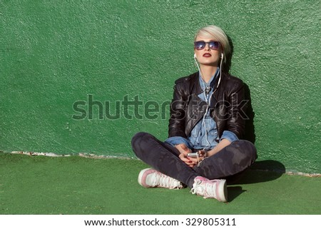 young blond woman with punk style hair using her mobile phone and leaning on green wall  - stock photo