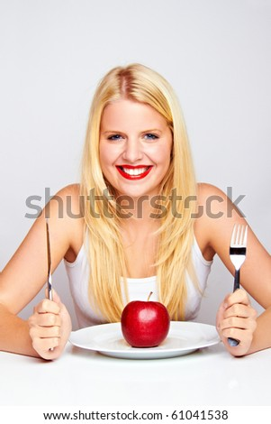 young blond woman with red apple on a plate with silverware - stock photo