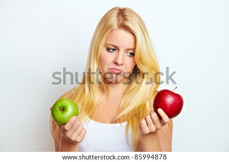 young blond woman with red apple on white ground