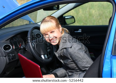 young blond woman with red notebook in a blue car. She is smiling - stock photo