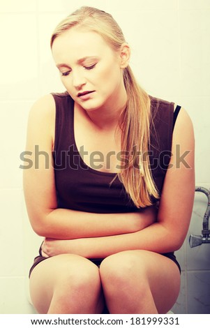Young blond woman with stomach issues in her bathroom at home  - stock photo