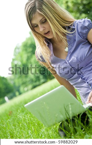 Young blond woman working with net-book outdoors in park on grass - surprise expression - stock photo