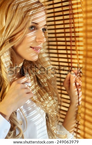 Young blonde beautiful happy woman looking looking out the window through the bamboo blinds with Sun hotspots on the face - stock photo