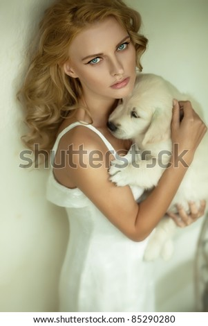 Young blonde beauty hugging a white puppy dog - stock photo