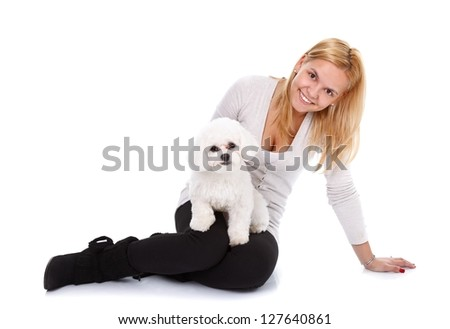Young blonde beauty sitting on the floor with a little puppy over white background