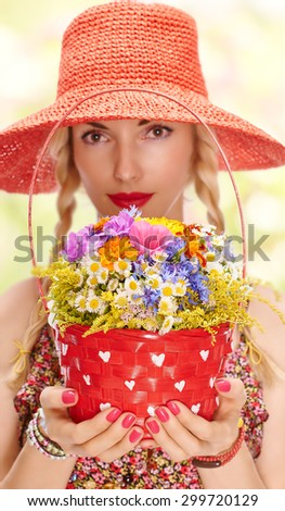Young blonde boho woman on summer meadow with red basket of vivid wildflowers in hands. Attractive joyful girl with red lips in orange beach hat. Romantic style, floral sundress. Bokeh - stock photo