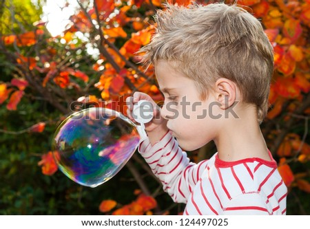 Young blonde boy blowing soap bubbles, autumnal background with orange leaves. back light situation. - stock photo