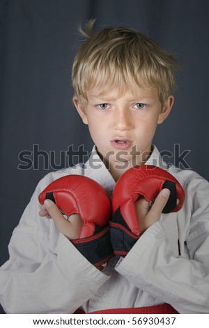 young blonde boy in karate outfit, red belt and pads