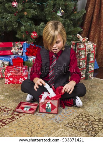 Young blonde boy opening gifts by the Christmas tree