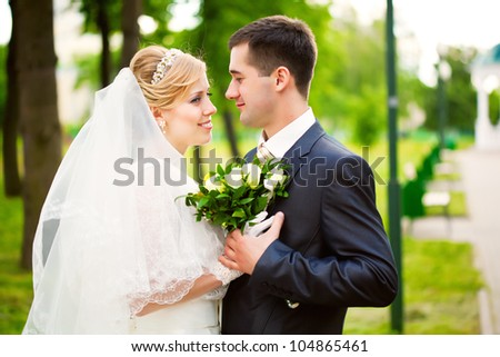 Young blonde bride and groom in walking the park - stock photo