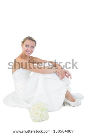 Young blonde bride sitting next to her bouquet smiling at camera - stock photo
