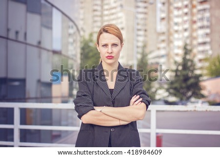 Young blonde business woman, arms crossed - stock photo