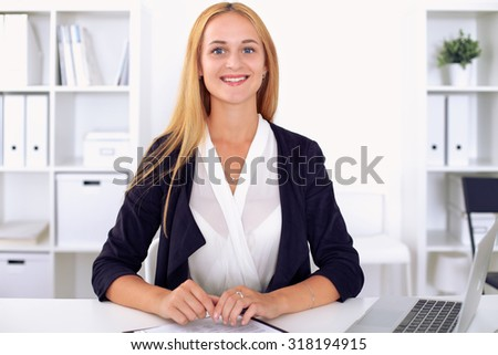 Young blonde business woman with laptop in the office - stock photo