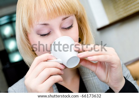 young blonde businesswoman drinks coffee, closeup - stock photo