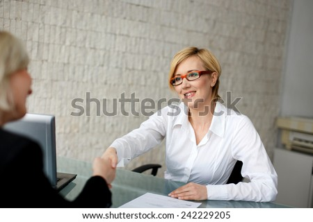 Young blonde businesswoman handshake, make contract in office - stock photo