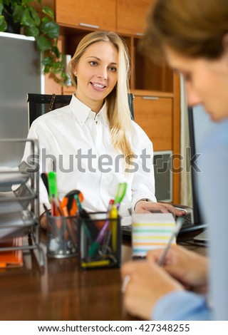 Young blonde businesswoman talking with colleague at office - stock photo