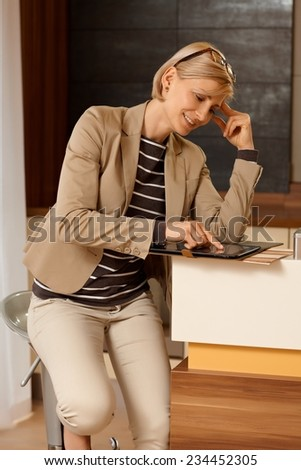 Young blonde businesswoman using tablet computer, sitting at counter. - stock photo