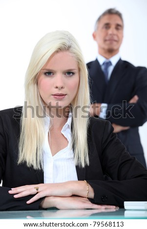 Young blonde businesswoman with older man in the background - stock photo