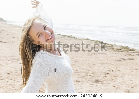 Young blonde carefree woman with arms outstretched on Atlantic beach in Prince Edward Island, Canada - stock photo