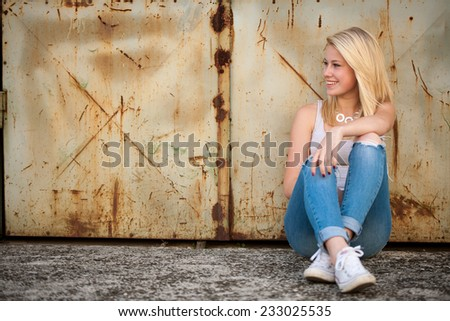 young blonde caucasian girl alone on a street in summer afternoon - stock photo