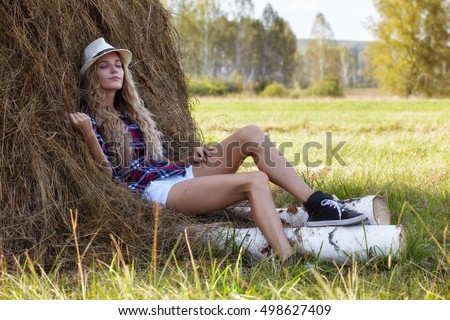 Young blonde country girl in hat sit near haystacks on birch log