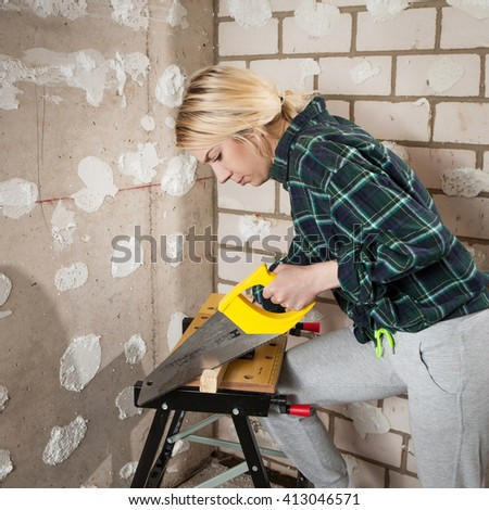 young blonde craftswoman cutting a wooden board with a handsaw indoors