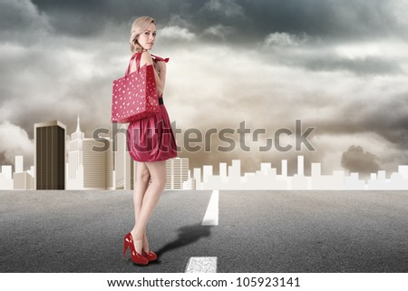 Young blonde fashion model with shopping bag - stock photo