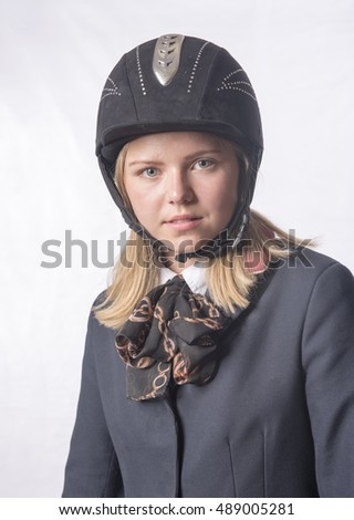 Young blonde female horse rider. Taken on a white background.