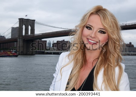 young blonde female in front of brooklyn bridge, nyc skyline - stock photo