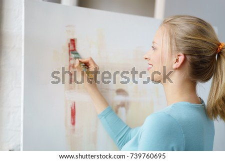 Young blonde female painter painting picture with brush in atelier