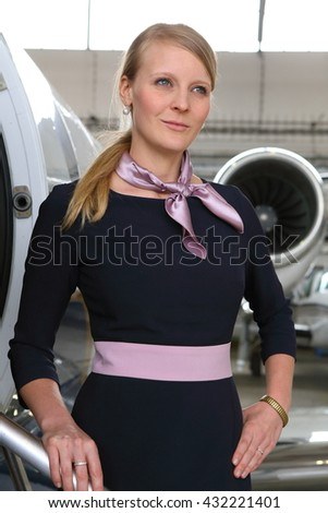 Young blonde flight attendant standing on the business plane steps  - stock photo
