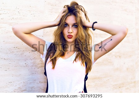 Young blonde funny hipster girl making grimaces and sending kiss near beige wall, positive mood. - stock photo