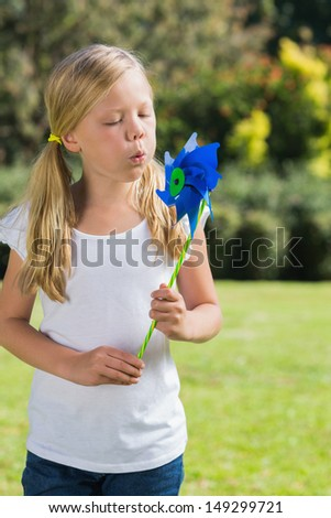 Young blonde girl blowing pinwheel in the park on sunny day