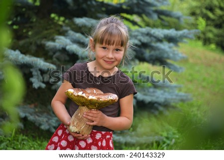 Young blonde girl holding a very large mushroom - stock photo