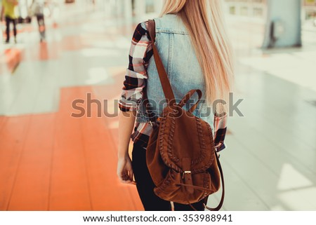 young blonde girl in a plaid shirt, jeans and black boots in sunglasses posing on the street standing on the bridge over the river smiling smodnaya Clothing Moscow city - stock photo