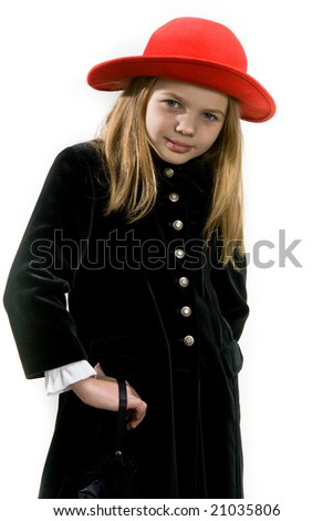 young blonde girl in dark winter coat  and red hat standing turned left body inclined