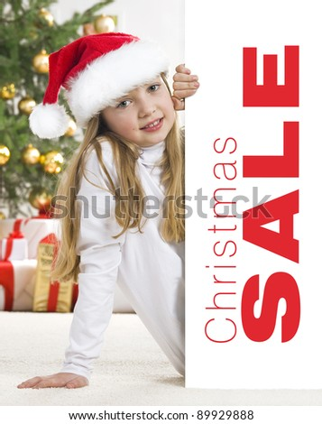 Young blonde girl in santa hat and red comforter behind white board