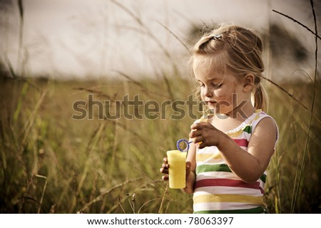 Young blonde girl is tired after playing outside all day - stock photo