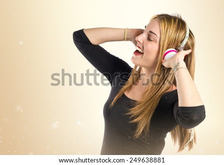 Young blonde girl listening music over ocher background  - stock photo